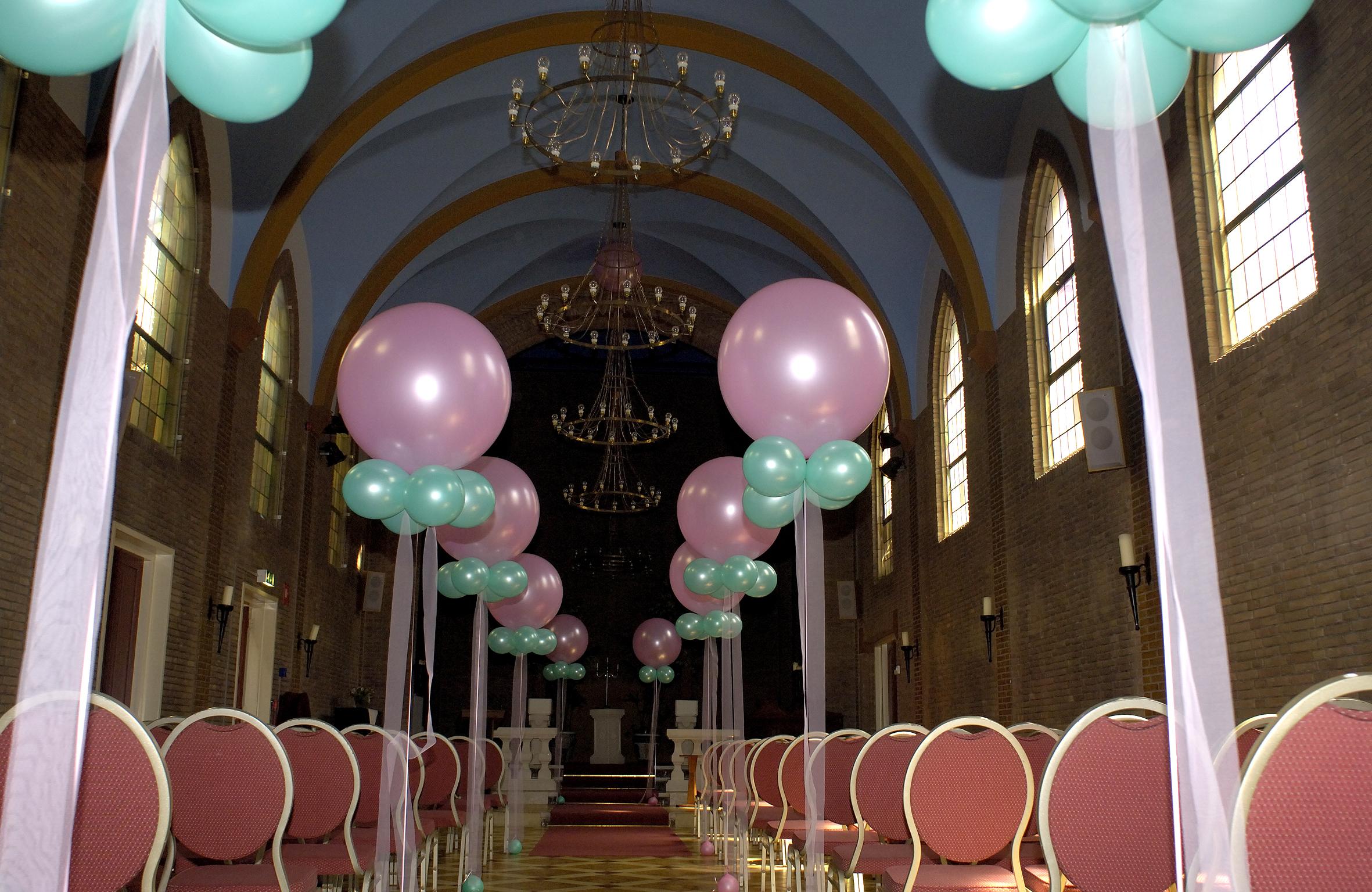 Ballonnendecoratie - Een grote heliumballon met kleinere ballonnen eronder en organzalint